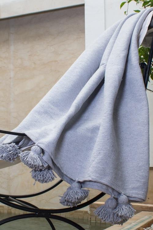 plaid à pompons en laine tissé a la main au maroc par des artisans pour une décoration bohème sur un canapé ou un lit